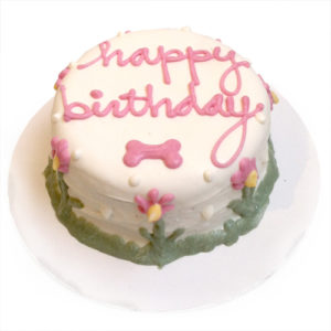 A white birthday cake decorated with the words happy birthday in pink,a pink bone and flowers