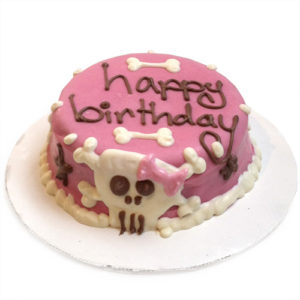 A pink cake decorated with the words Happy Birthday, and a skull & crossbones wearing a pink bow