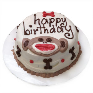 A white cake decorated with the words happy birthday, and a drawing of a monkey