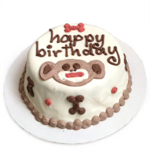 A white cake cake decorated with the words happy birthday, and a drawing of a monkey
