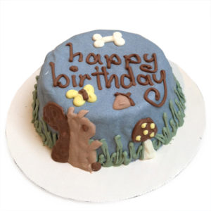 a blue birthday cake decorated with the words Happy Birthday, a squirrel, a mushroom, a bone, an acorn, and a butterfly