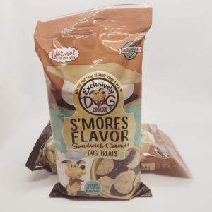 The front of a package of Exclusively Dog brand Smores Flavor Sandwich Cremes dog treats. The bag has a drawn picture of a dog wearing a chefs hat and red handkerchief and the following information: Made with natural ingredients, Baked in the USA, Baked in small batches