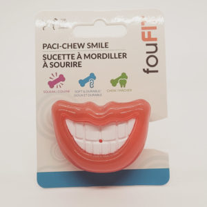 A FouFit brand Red PaciChew Smile Dog Toy. The toy is shaped like a pacifier, with the outward-facing end made into a wide grin.